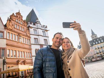 Ansicht auf ein Paar, welches beim Flanieren über den Hauptmarkt in Trier gerade ein Selfie macht.