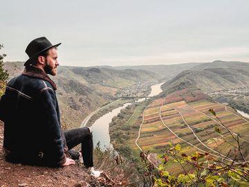 Ein Wanderer mit Mütze schaut sitzend ins Moseltal vom Höhenzug Calmont herab.